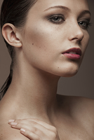 Thoughtful beauty headshot of young brunette woman with freckles and natural make-up