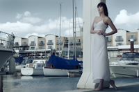 Relaxed summer portrait of East Asian fashion model in white dress against a backdrop of boats at the marina