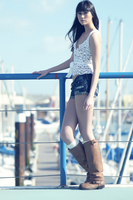 Casual full length portrait of East Asian fashion model on a sunny day at the marina