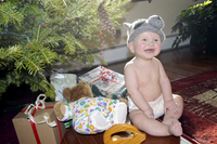 Laughing baby under tree with raccoon hat