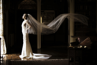 A bride looking out a window with a very long veil