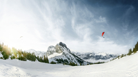 panoramic view of a snowy mountain on a sunny day with two Para gliders in the sky