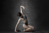 ballerina performing sitting down on textured background