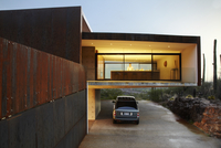Cantilevered Lit Kitchen And Carport Exterior Of Modern Home, Ventana Canyon House By Architect Rick Jo At Dusk..