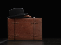 Brown Leather Case With A Formal Man'S Hat Lying On It