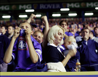 Mother, Baby With Bottle And Son Cheering, Football Supporters In Crowd At English Premiership Match