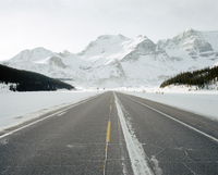 A road in winter points towards a mountain.