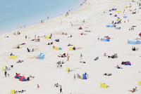 Dozens of holidaymakers sunbathe and relax on Porthminster Beach early one summer's morning.