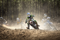 Motocross racers tear around the 1st turn during a race
