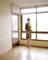 Retro style woman by a window in an empty room