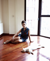 Retro style woman sitting down in an empty room with a cat 20055019824| 写真素材・ストックフォト・画像・イラスト素材|アマナイメージズ