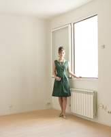 Retro style woman standing by a window in an empty room