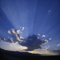 Sunset with rays of sunlight from behind large cloud over desert