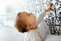 10-month-old boy looks at decorative wallpaper.