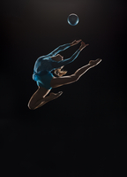 Athletic Olympic rhythmic gymnast leaping in mid air with ball