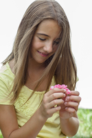 A young girl smiles while holding a small flower. 20055020095| 写真素材・ストックフォト・画像・イラスト素材|アマナイメージズ
