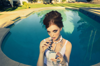 Fashionable decadent young woman in a white bathing suit and costume sitting at a luxurious pool with zebra sunglasses texting o