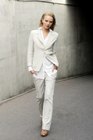 Young woman in linen suit walking down a street