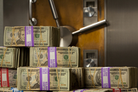 Bundled American currency in front of a bank vault