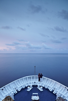 Couple on bow at sunset on cruise ship