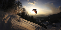 Snowboarder jumping at sunset with village below