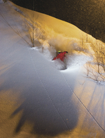 Snowboarder turns in powder at night