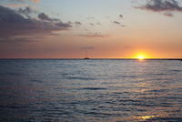 The sun setting over the sea with a yacht in the foreground 20055020794  写真素材・ストックフォト・画像・イラスト素材 アマナイメージズ