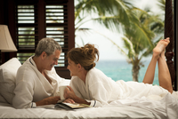 mature couple in bath robes lying on bed in resort
