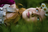 Girl with crown of daisies lays in grass.
