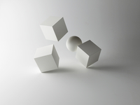 Tumbling Cubes and Sphere on White Background