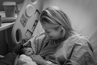 Newborn baby and mother looking at one another in hospital bed.
