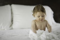 Nude baby playing in bed sheets