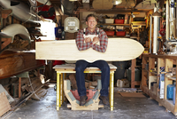 Portrait of a woodworker with a handmade wooden surfboard in his garage workshop.
