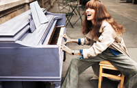 A purple piano found outside on the street and a red headed female model loves to play.