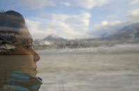 Young woman looking out train window with reflection of passing landscape. 20055021305| 写真素材・ストックフォト・画像・イラスト素材|アマナイメージズ