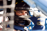 Intense headshot of race car driver in cockpit signaling with his thumb