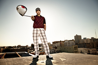 Portrait of golfer on roof pointing at camera with driver.