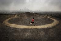 Male runner mid stride on u shaped path overlooking modern city scape. 20055021407| 写真素材・ストックフォト・画像・イラスト素材|アマナイメージズ