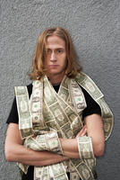 Portrait of caucasian male in 20s with long hair and covered in dollar bills.