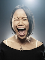 Portrait of Asian woman yelling at the top of her lungs..