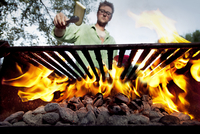 Man placing veggie on bbq.