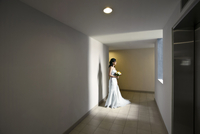A young female bride standing alone at the corridor with a bouquet of flowers.