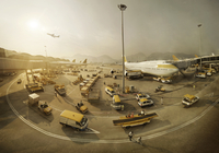 Planes parked up in Hong Kong airport with baggage handlers on runway.