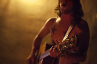 Shirtless man with tattoos singing and playing acoustic guitar at a backyard party