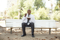 Middle age African American office worker eating lunch outdoors on a park bench
