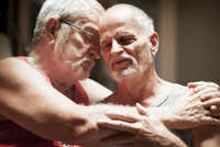 Portrait of an older gay couple hugging one another with their eyes closed 20055021892| 写真素材・ストックフォト・画像・イラスト素材|アマナイメージズ
