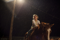 Portrait of a happy young girl on horseback at night in the rain
