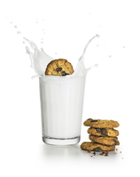 Chocolate chip cookies splashing into a cup of milk with a big splash and a stack of cookies on the surface