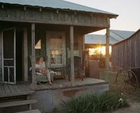 Woman sat on porch of shack in Mississippi with sun glaring 20055022148| 写真素材・ストックフォト・画像・イラスト素材|アマナイメージズ