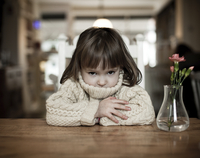 Girl toddler sitting at a table in a cafe with arms crossed and mouth hidden inside her wooly jumper